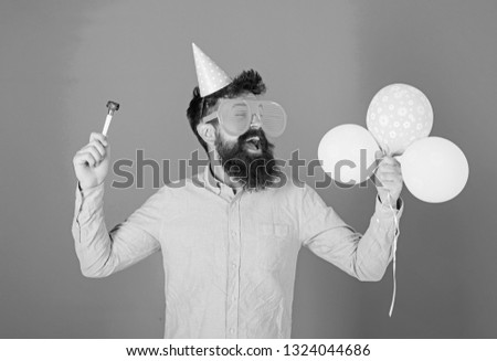 Man with beard and mustache on happy face holds air balloons, blue background. Party concept. Guy in party hat with holiday attributes celebrates. Hipster in giant eyeglasses celebrating birthday. #1324044686