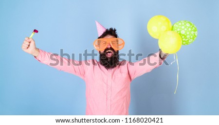 Man with beard and mustache on happy face holds air balloons, light blue background. Party concept. Guy in party hat with holiday attributes celebrates. Hipster in giant glasses celebrating birthday.