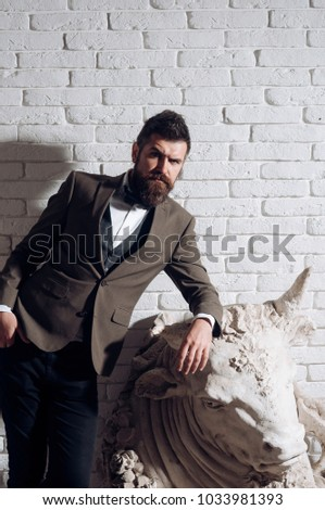 Man with beard and mustache on white brick wall background. Hipster with strict face in suit abuts on sculpture of bull. Masculinity and brutality concept. Guy near piece of art - sculpture of bull. #1033981393