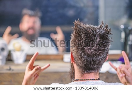 Man with beard and mustache sits in hairdressers chair in front of mirror background. Hipster with wet hair waits for haircut, rear view. Reflexion of bearded client of barbershop. Barbershop concept.