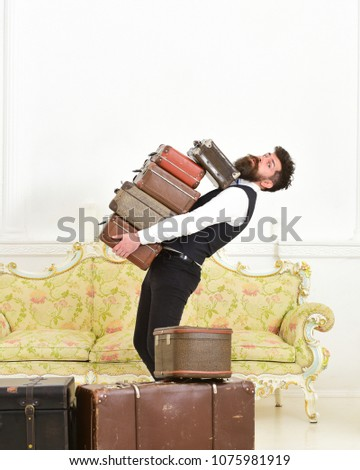Man with beard and mustache wearing classic suit delivers luggage, luxury white interior background. Butler and service concept. Macho, elegant porter carries heavy pile of vintage suitcases. #1075981919