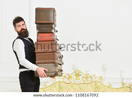 Man with beard and mustache wearing classic suit delivers luggage, luxury white interior background. Macho, elegant porter carries heavy pile of vintage suitcases. Butler and service concept. #1108167092
