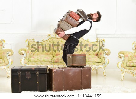 Man with beard and mustache wearing classic suit delivers luggage, luxury white interior background. Macho, elegant porter carries heavy pile of vintage suitcases. Butler and service concept. #1113441155