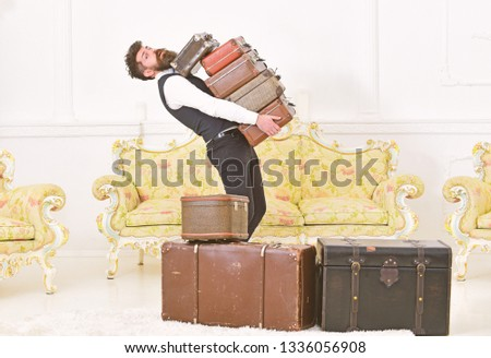 Man with beard and mustache wearing classic suit delivers luggage, luxury white interior background. Macho, elegant porter carries heavy pile of vintage suitcases. Butler and service concept. #1336056908