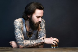man with beard and tattoo. man drink whiskey. bearded hipster boy in Bar. alcoholism