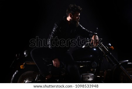 Man with beard, biker in leather jacket lean on motor bike in darkness, black background. Biker culture concept. Macho, brutal biker in leather jacket stand near motorcycle at night time, copy space #1098533948