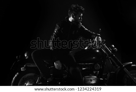 Man with beard, biker in leather jacket lean on motor bike in darkness, black background. Biker culture concept. Macho, brutal biker in leather jacket stand near motorcycle at night time, copy space. #1234224319