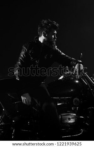 Man with beard, biker in leather jacket lean on motor bike in darkness, black background. Brutality and masculine concept. Macho, brutal biker in leather jacket stand near motorcycle at night time. #1221939625