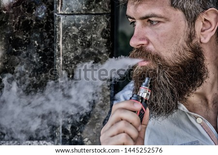 Man with beard breathe out smoke. Smoking electronic cigarette. Stress relief concept. Smoking device. Man long beard relaxed with smoking habit. Clouds of flavored smoke. Bearded man smoking vape.