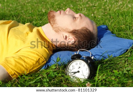 man with beard in yellow shirt sleeping on summer meadow near clock, lying on back, rest concept