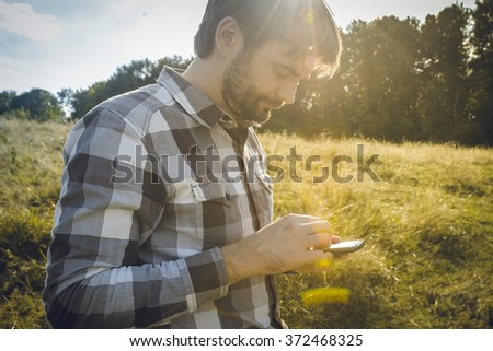 Man with beard looking at his smartphone while sundown Bearded man texting sms on his phone Man using apps for travel or gps navigation help or reading news and texts using 3g and 4g Photo stock ©