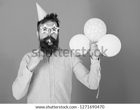Man with beard on calm face holds air balloons, blue background. Surprise concept. Hipster in star shaped glasses blows into party horn. Guy in party hat with holiday attributes celebrates. #1271690470