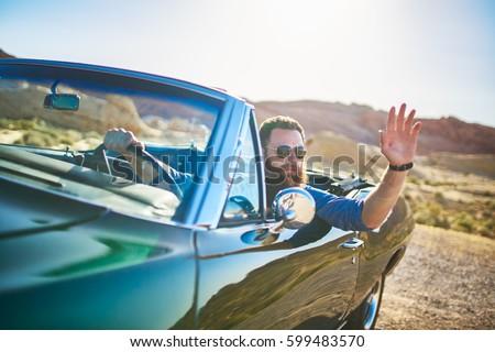 man with beard sitting in vintage car waving