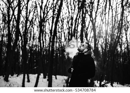 Man with beard smoke electronic cigarette outdoor #534708784