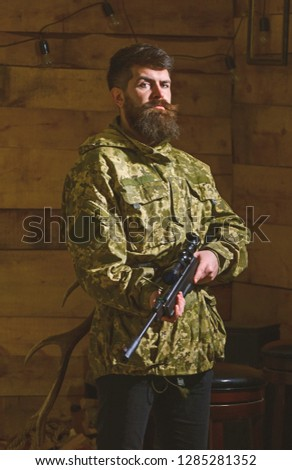 Man with beard wears camouflage clothing, wooden interior background. Hunter, brutal hipster with gun ready for hunting. Huntsman concept. Macho on strict face at gamekeepers house. #1285281352