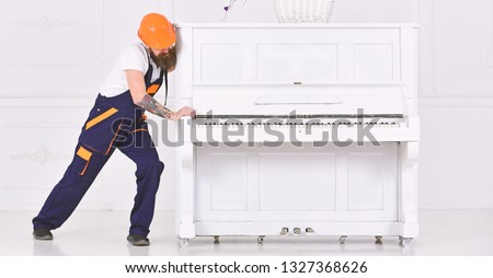 Man with beard worker in helmet and overalls pushes, efforts to move piano, white background. Loader moves piano instrument. Courier delivers furniture, move out, relocation. Heavy loads concept. #1327368626