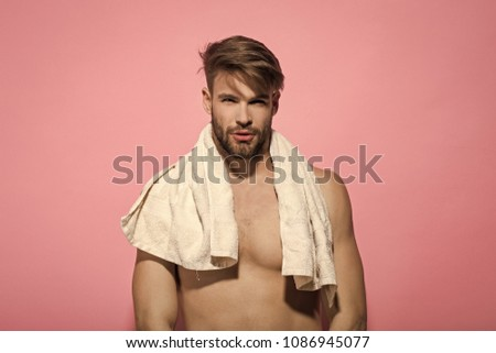 Man with bearded face, stylish hair, bath towel on muscular torso on pink background. Beauty, grooming, hygiene. Health, fitness, bodycare concept #1086945077