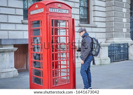 man with beret in front of a phone booth