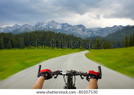 Man with bicycle riding mountain road