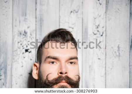 Man with big curved mustache, close-up portrait on pale white painted wooden background. Shallow depth of field.