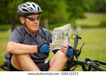 Man with bike checking map and looking around.