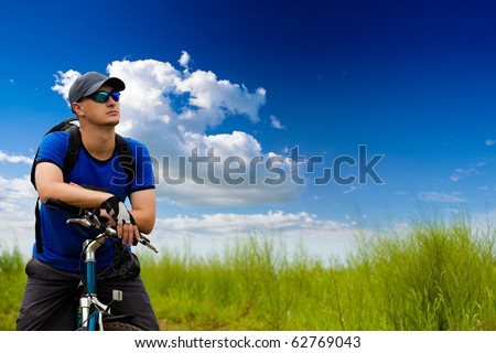 man with bike on green field under blue skies - stock photo