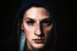 Man with black eyes on dark black background