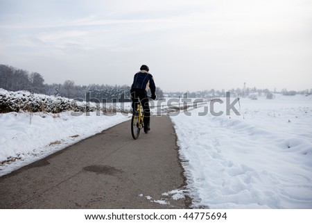 man with black helmet riding a bicycle in a snowy landscape