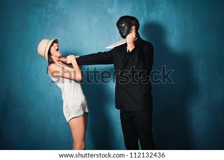 man with black mask attack young girl with knife studio shot