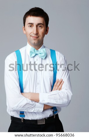 Man with blue bow tie standing with his arms folded.
