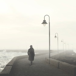 man with bowler and coat walking in a foggy street in winter