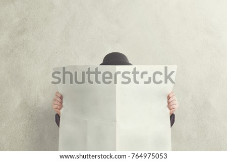 man with bowler holding empty newspaper