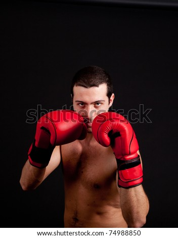 Man with boxing gloves on black background