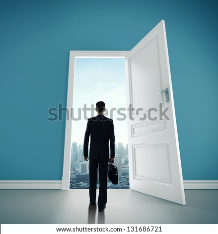 man with briefcase and open door to city