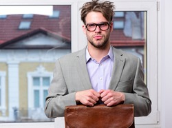 Man with briefcase isolated on white background. Nerd or brainiac wearing classic jacket. Bookworm syndrome and hard work concept. Serious teacher or worker with bristle in nerd glasses.