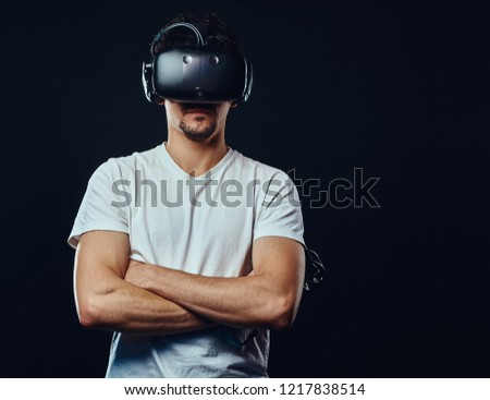 Man with bristle dressed in white shirt playing games with virtual reality goggles. #1217838514
