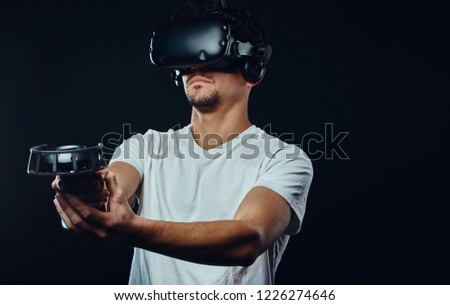 Man with bristle dressed in white shirt playing games with virtual reality goggles. #1226274646