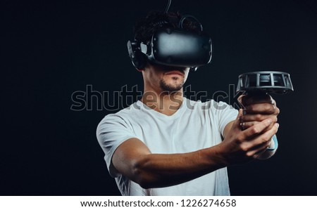 Man with bristle dressed in white shirt playing games with virtual reality goggles. #1226274658