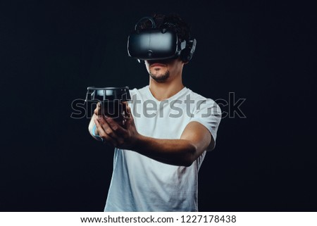 Man with bristle dressed in white shirt playing games with virtual reality goggles. #1227178438