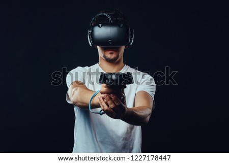 Man with bristle dressed in white shirt playing games with virtual reality goggles. #1227178447