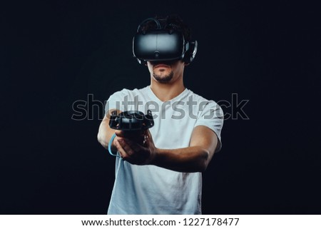Man with bristle dressed in white shirt playing games with virtual reality goggles. #1227178477