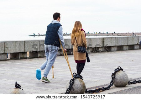 man with broken leg on crutches walks along the promenade with girl. Bone fracture and ankle fracture #1540725917