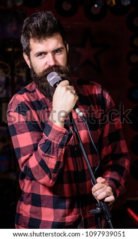 Man with calm face holds microphone, singing song, black background. Guy likes to sing rock songs. Musician with beard and mustache singing song in karaoke. Vocalist concept #1097939051