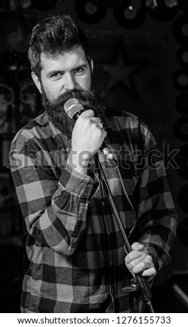 Man with calm face holds microphone, singing song, black background. Guy likes to sing rock songs. Musician with beard and mustache singing song in karaoke. Vocalist concept. #1276155733
