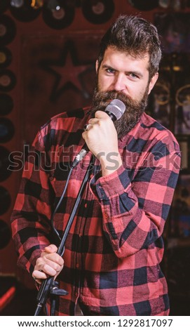 Man with calm face holds microphone, singing song, black background. Guy likes to sing rock songs. Musician with beard and mustache singing song in karaoke. Vocalist concept. #1292817097