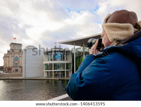 Man with camera at Reichstag building with German Flags in Berlin, capital of Germany in winter in the street. German Bundestag parliament house. #1406413595
