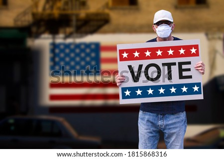 Man with cap blue jeans and medical mask holding a cardboard sign text VOTE with american stars and stripes flag on a wall in the background. American Presidential patriotic background election day. Stockfoto ©