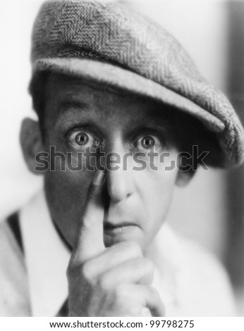 Man with cap putting his finger to nose
