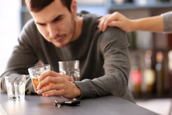 Man with car key and alcoholic beverage in bar. Don't drink and drive concept