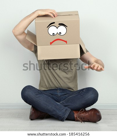 Man with cardboard box on his head sitting on floor near wall - stock photo